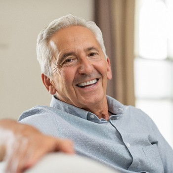 An older man sitting on a couch smiling