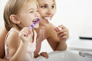A mother and daughter brushing their teeth together.